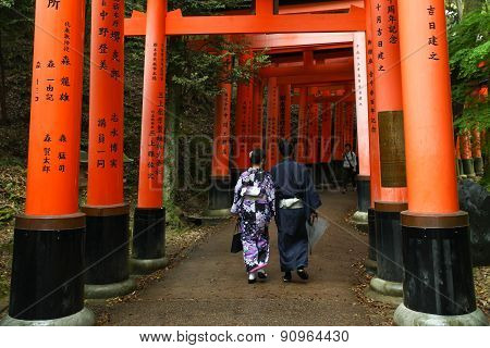 Japanese Geisha and partner at Fushimi Inari Shrine gardens  in Kyoto