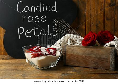 Chalkboard with inscription Candied Rose Petals, sugar and rose petals.