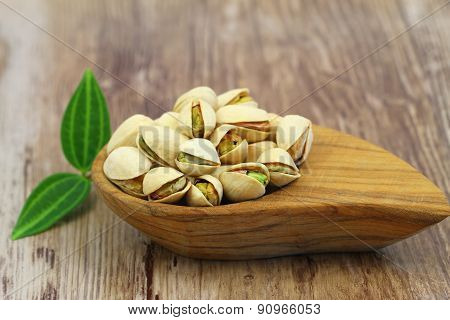 Pistachio nuts in bamboo bowl on wooden surface