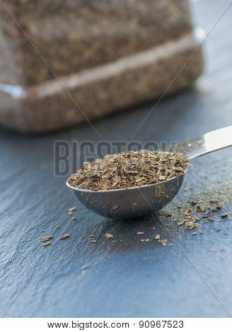 A teaspoon full of dried basil leaf