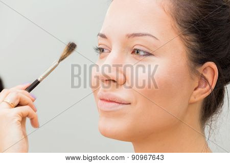 Application of powder on the model's face.