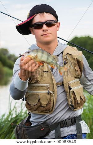 Young fisherman on the river bank.