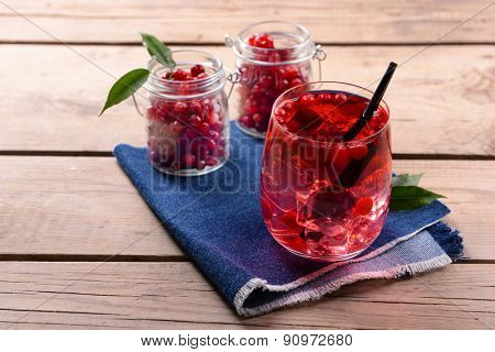 Compote with red currant in glassware on jeans cloth on wooden background
