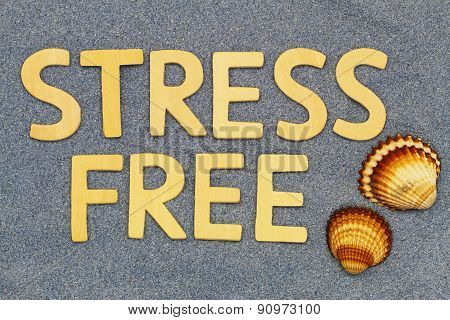 Stress free written with wooden letters on blue sand