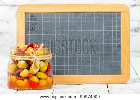 Glass Jar With Olives And Peppers With Blackboard