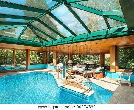 Interior of a residential house, large indoor pool, ceiling with skylights
