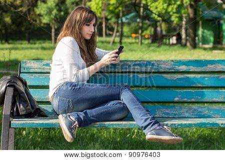 Pretty Young Woman Using Smartphone Sitting On Bench