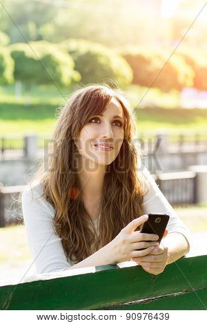 Dreaming Young Beautiful Woman With Phone On Bench