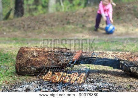 Camping grill with chicken meat cooking on campfire with playing toddler girl is at background