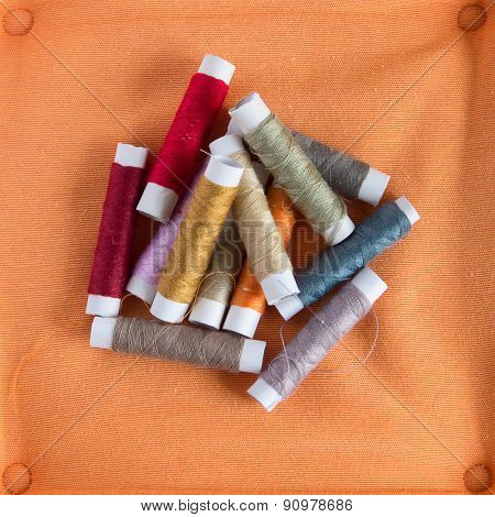 Colored Sewing Threads On A Orange Background