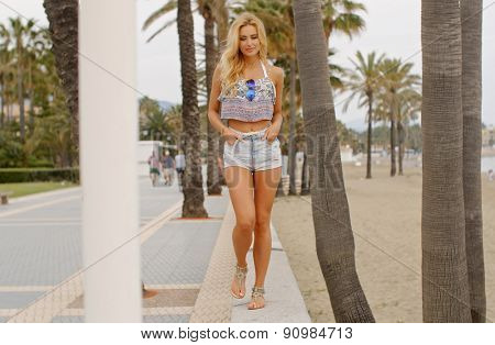 Full Length Front View of Blond Woman Wearing Denim Cut Offs Walking Toward Camera on Beach Front Promenade
