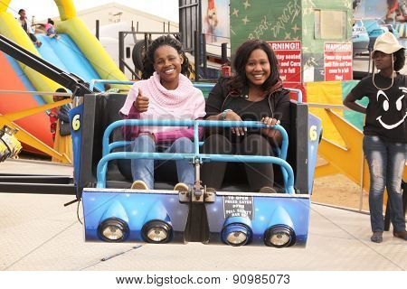 Black African Female Friends Enjoying Electronic Roundabout Ride