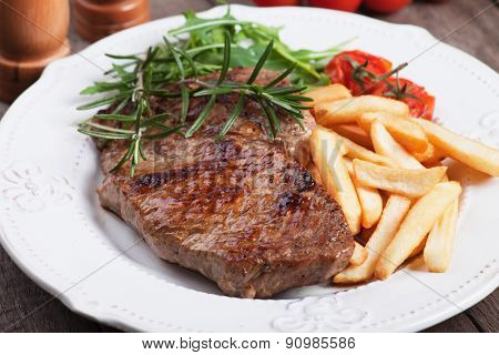 Beef rib-eye steak with french fries, rosemary and rocket salad