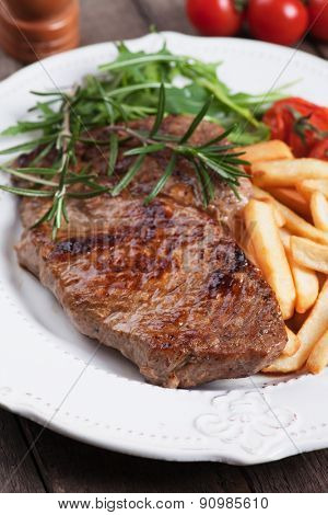 Beef rib-eye steak with french fries,rosemary and rocket salad