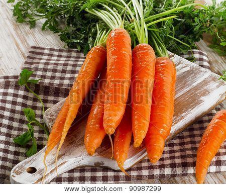 Fresh Carrots With Green Leaves On A Wooden Table