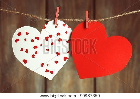 Bright hearts hanging on rope on wooden background