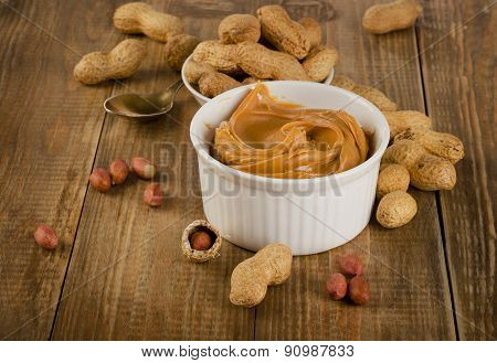Peanut Butter With Peanuts On A Rustic Wooden Table.