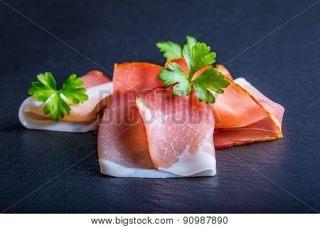 Curled Slices of Delicious Prosciutto with parsley leaves on granite background