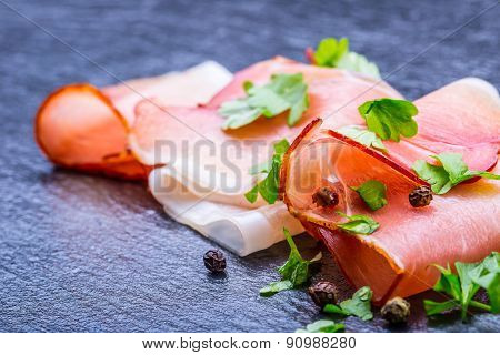 Curled Slices of Delicious Prosciutto with parsley leaves on granite board.