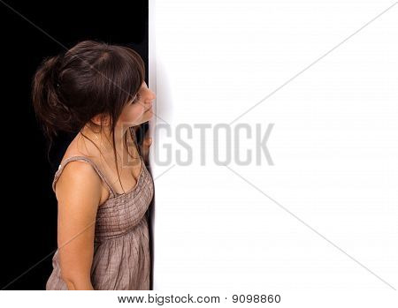 Portrait Of A Young Woman Peeking Behind Empty Wall