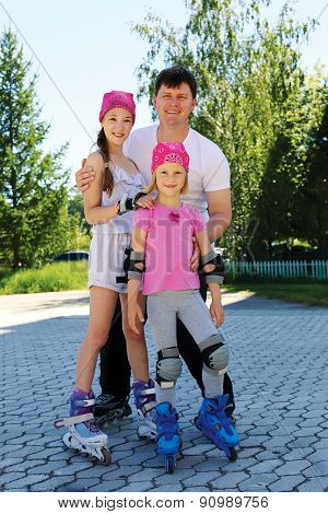Daddy And Two Daughters Skate On Roller Skates On A Warm Summer Day