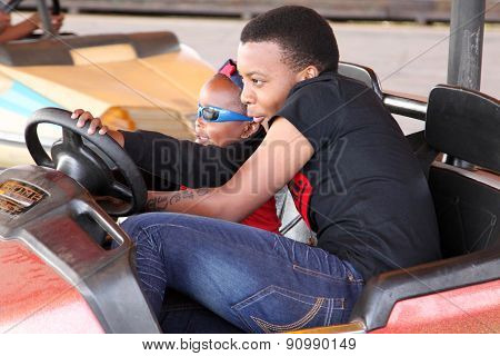 Black African Brother And Sister Enjoying Bumper Cars