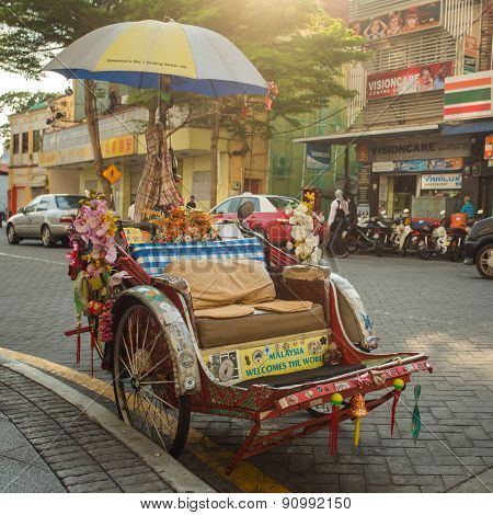 Penang, Malaysia - February 25, 2015: An old traditional trishaw cab along a street in Penang, Malaysia.