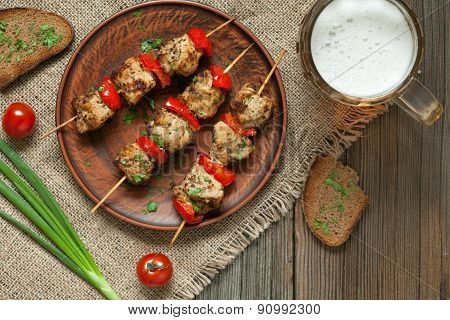 Delicious roasted turkey or chicken kebab skewers meat barbecue on clay dish with tomatoes and beer