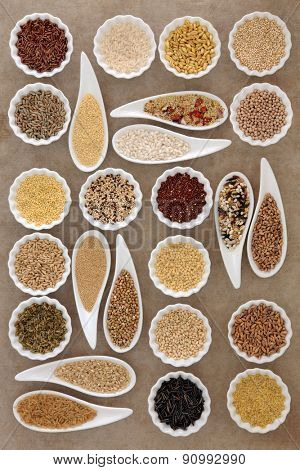 Large cereal and grain food selection in porcelain dishes over old brown paper background.