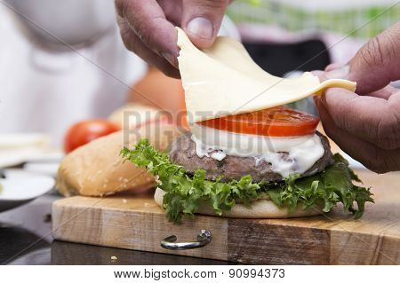 Close Up Chef Putting Slice Of Cheese On The Hamburger Bun