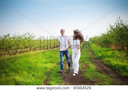 Young Couple Having Fun On The Cherry Garden In The Spring