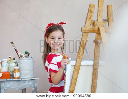 Little Artist Girl Holding A Paintbrush And Looking Over A Canvas