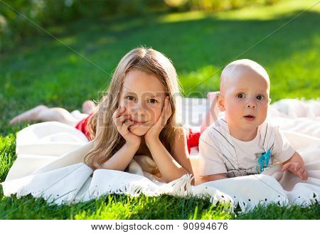 Two Children On Green Meadow And Smile