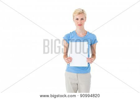 Stern blonde woman holding sheet of paper on white background