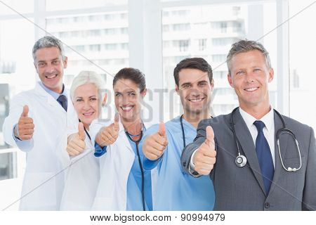 Portrait of confident doctors in row thumbs up in the hospital