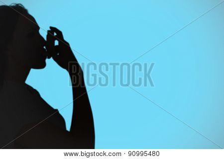 Asthmatic brunette using her inhaler against blue background with vignette
