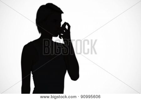 Blonde woman taking her inhaler against white background with vignette