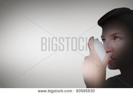 Blonde woman taking her inhaler against grey vignette