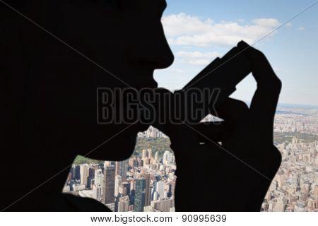 Blonde woman taking her inhaler against new york