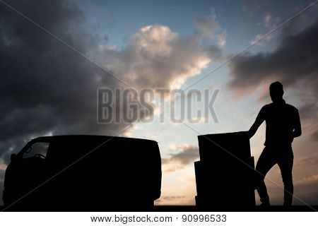 Delivery man with cardboard boxes against blue and orange sky with clouds