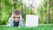 picture of sad boy  - young sad boy with laptop computer on green grass in the park - JPG