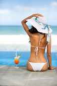 stock photo of beach hat  - beach hat rear view woman with cocktail on tropical beach - JPG