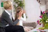 stock photo of grandma  - girl with  grandma sitting on sofa at home and  waving a greeting - JPG
