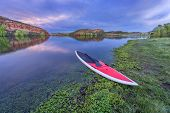 pic of horsetooth reservoir  - dusk over calm lake with a red stand up paddleborad  with a paddle on shore  - JPG