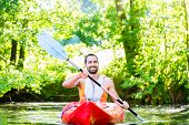 stock photo of canoe boat man  - Man paddling with kayak on river for water sport - JPG