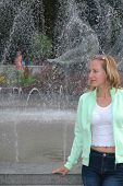 stock photo of gushing  - portrait of young pretty woman near city fountain - JPG
