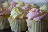 image of sprinkling  - This is a photograph of Vanilla cupcakes topped with Pink and Yellow buttercream - JPG
