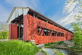 foto of covered bridge  - An old red covered bridge in Scipio Indiana crosses Sand Creek under a blue cloudy sky - JPG