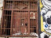 stock photo of lockups  - Grungy window with rusty iron bars in an urban downtown area - JPG
