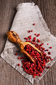 picture of peppercorns  - Red peppercorns in wooden scoop on burlap - JPG